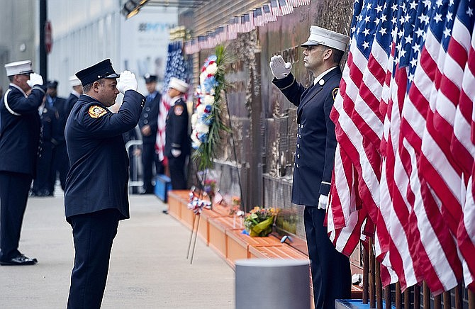 In this Sept. 11, 2018 photo, New York City firefighters salute in front of a memorial on the side of a firehouse adjacent to One World Trade Center and the 9/11 Memorial site. (Craig Ruttle/AP, File)