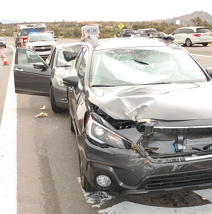 Two vehicles in the left turn lane of Pioneer Parkway sit damaged Friday morning, Sept. 11, 2020, in Prescott, after being hit by loose parts that fell from a truck's trailer. (Tim Wiederaenders/Courier)
