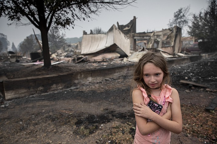 Ellie Owens, 8, from Grants Pass, Ore., looks at fire damage Friday, Sept. 11, 2020, as destructive wildfires devastate the region in Talent, Ore. (Paula Bronstein/AP)