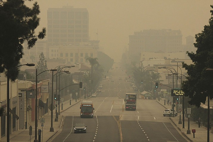 Smoke from wildfires fills the sky over Pasadena, Calif., in this view looking east down Colorado Boulevard in a Saturday, Sept. 12, 2020 file photo. The fires consuming the forests of California and Oregon and darkening the skies over San Francisco and Portland are also damaging an economy already struggling with the coronavirus outbreak. In the communities where they are raging, wildfires are destroying property, running up huge losses for property insurers and putting a strain on economic activity that could linger for a year or more. (AP Photo/John Antczak, File)