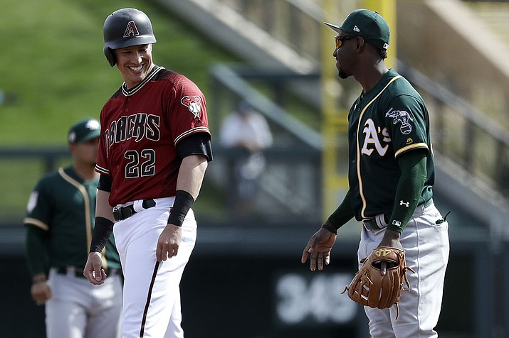 Arizona Diamondbacks' Jake Lamb (22) laughs with Oakland Athletics shortstop Jorge Mateo during the second inning of a spring baseball game in Scottsdale, Ariz., Monday, Feb. 25, 2019. Lamb was signed by the A's Monday after being designated for assignment by the Diamondbacks last week. (AP Photo/Chris Carlson)