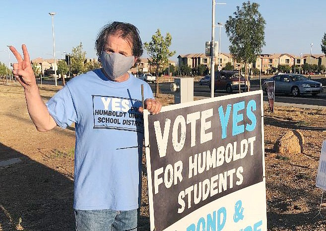 """Liberty Traditional School teacher Al Zalfini of the Humboldt Unified School District stands next to his sign asking for a """"Yes"""" vote for the bond and override. (HUSD/Courtesy)"""