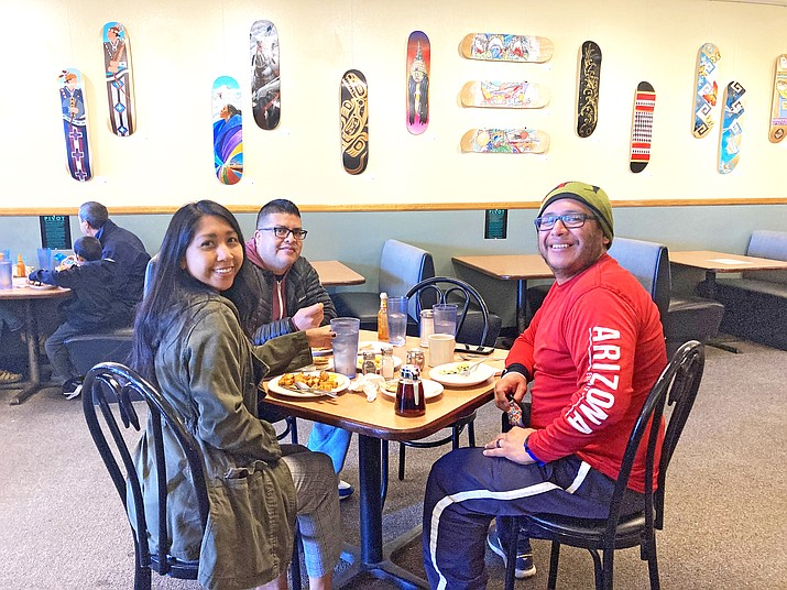 Pivot exhibit manager Samantha Honanie eats breakfast with Pivot creators Duane Koyawena and Landis Bahe at Brandy's in Flagstaff admist the new pop-up exhbit, which is on display at the restaurant until Nov. 4. (Katherine Locke/NHO)