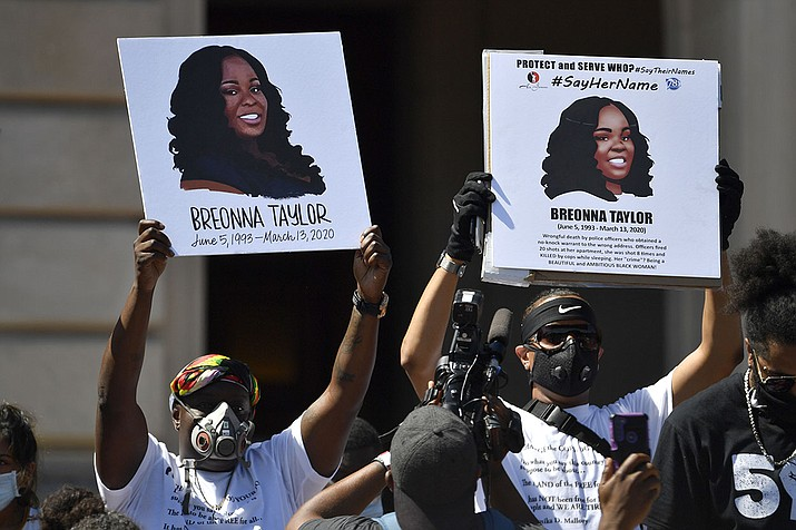 Signs are held up showing Breonna Taylor during a rally in her honor on the steps of the Kentucky State Capitol in Frankfort, Ky., Thursday, June 25, 2020. The city of Louisville will pay $12 million dollars to the mother of  Taylor and install police reforms as part of a settlement of a lawsuit from Taylor's family, The Associated Press has learned. (Timothy D. Easley, AP File)