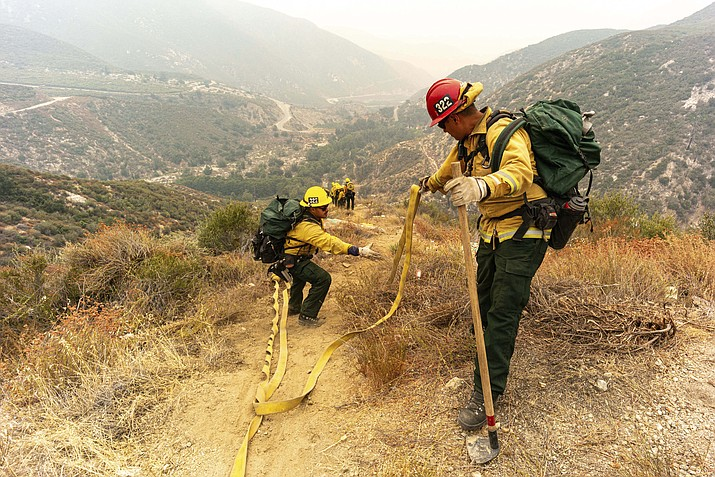 Fire crews from Arizona lay hose line down rugged terrain off Highway 39 near Crystal Lake in front of the Bobcat Fire, in California, which has burned more than 23,000 acres, Thursday, Sept. 10, 2020. (David Crane/The Orange County Register via AP)