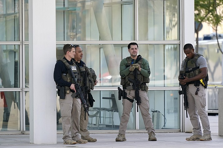 Federal law enforcement personnel stand outside the Sandra Day O'Connor Federal Courthouse Tuesday, Sept. 15, 2020, in Phoenix. A drive-by shooting wounded a federal court security officer Tuesday outside the courthouse in downtown Phoenix. The officer was taken to a hospital and is expected to recover, according to city police and the FBI, which is investigating. (Ross D. Franklin/AP)