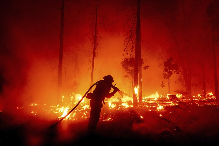 A firefighter battles flames threatening homes in Madera County, California. (Noah Berger/AP, File)
