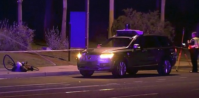In this March 19, 2018, file image taken from video provided by ABC-15, an investigators works at the scene of a fatal accident involving a self driving Uber car in Tempe, Ariz. Police outside Phoenix recently closed part of a street to conduct a lighting test as an investigation continues into the 2018 death of a woman who was struck and killed by an Uber self-driving SUV. The Maricopa County Attorney's Office says prosecutors asked for more investigation before making a decision about whether to charge backup driver Rafaela Vasquez who was supposed to take control in an emergency. Another prosecutor's office decided in March not to charge Uber. (ABC-15.com via AP)