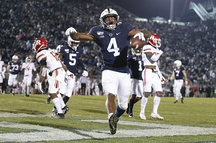 In this Nov. 30, 2019, file photo, Penn State running back Journey Brown (4) celebrates his third quarter touchdown run against Rutgers during an NCAA college football game in State College, Pa. Big Ten is going to give fall football a shot after all. Less than five weeks after pushing football and other fall sports to spring in the name of player safety during the pandemic, the conference changed course Wednesday, Sept. 16, 2020, and said it plans to begin its season the weekend of Oct. 23-24. (Barry Reeger, AP File)