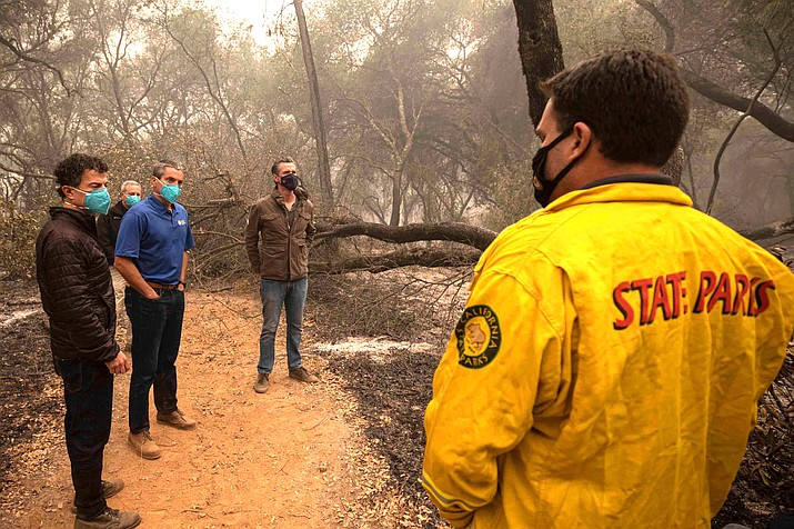 California Gov. Gavin Newsom stands near charred trees in Oroville to address wildfires ravaging his state, which he blames on man-made climate change. (Photo courtesy of California Environmental Protection Agency)