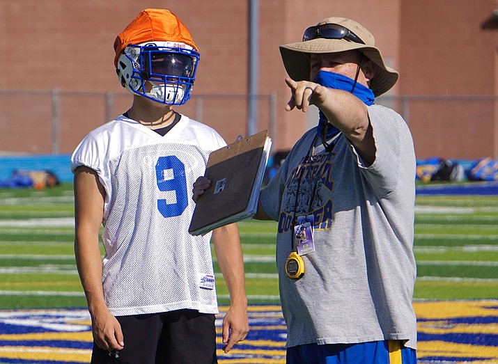 Prescott football head coach Cody Collett guides senior wide receiver Nathan Briseno during practice. The Badgers are coping with pandemic protocols and other challenges for the 2020 season. (Aaron Valdez/Courier)