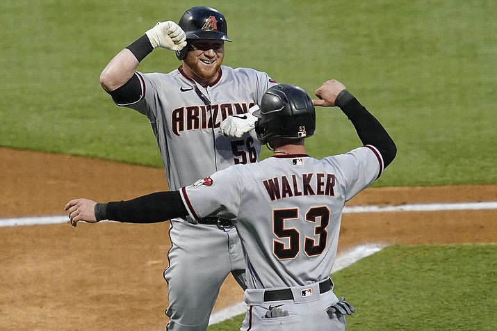 Arizona Diamondbacks' Kole Calhoun, left, celebrates a two-run home run with Christian Walker during the first inning of the team's baseball game against the Los Angeles Angels on Tuesday, Sept. 15, 2020, in Anaheim, Calif. (Ashley Landis/AP)