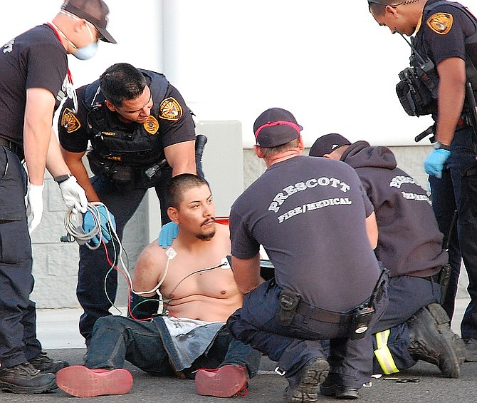 First responders treat Alfredo Saldivar, 28, who was captured by police Wednesday night, May 13, 2020, after he fled from officers at speeds reaching 120 mph and striking cars. (Tim Wiederaenders/Courier)