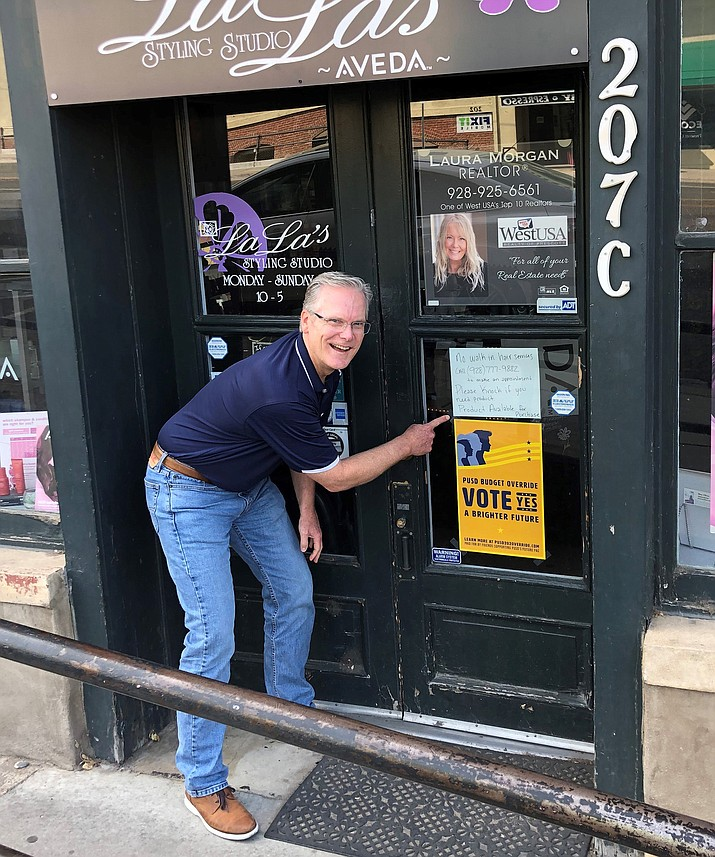 "Friends of Prescott Unified School District's Future Political Action Committee Chairman Scott Fagin points out a ""Vote Yes"" poster at a downtown Prescott business. The Friends group is working to get voters to approve a budget override for PUSD. (Courtesy)"