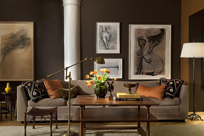 New York-based designer Glenn Gissler painted this New York loft in Benjamin Moore's deep, rich Van Buren Brown, with columns and ceilings in crisp Decorator's White. A long tuxedo-style sofa in milk chocolate-y velvet anchors the space along with tonal modern art. The result is a chic, contemporary yet cozy and eminently livable space. (Gross & Daley/Glenn Gissler via AP)