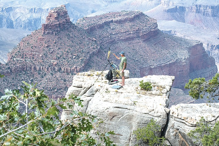 Prescott artist Bill Cramer paints from a ledge on the South Rim during the 12th annual Celebration of Arts at the South Rim of Grand Canyon National Park. (V. Ronnie Tierney/WGCN)