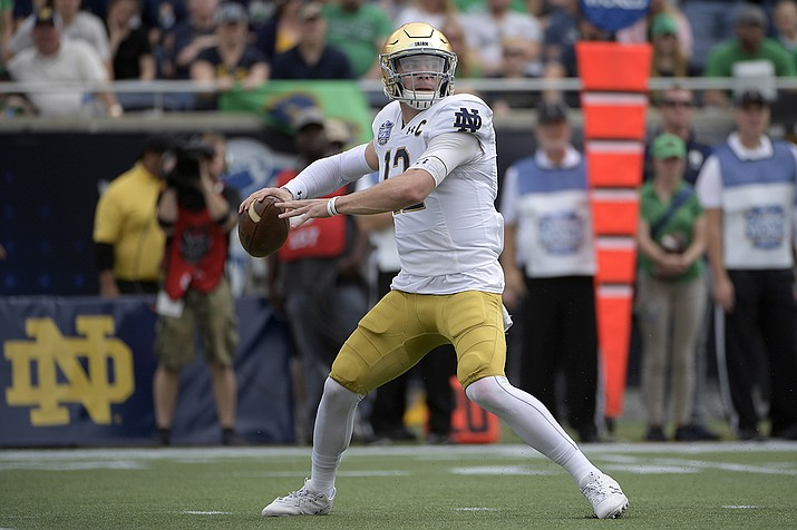 File-Notre Dame quarterback Ian Book (12) throws a pass during the first half of the Camping World Bowl NCAA college football game against Iowa State Saturday, Dec. 28, 2019, in Orlando, Fla. Notre Dame's game at Wake Forest on Saturday has been postponed after positive COVID-19 tests landed 13 Fighting Irish players in isolation and another 10 in quarantine. (Phelan M. Ebenhack, AP File)
