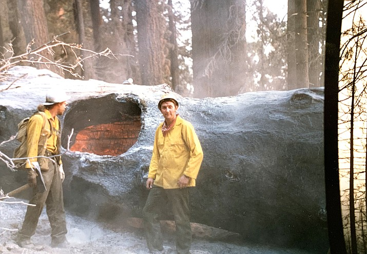 Wildland firefighter Kim Brown (right) poses for a picture next to a smoldering tree during a wildland fire assignment in the 1980s. (Photo courtesy of Kim Brown)