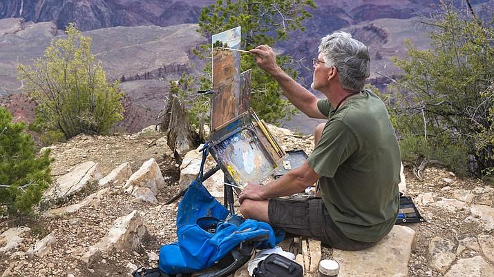 Highlands Center Bill painting seated on a rock Prescott Plein Air Art Festival.