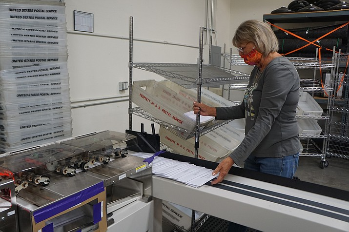 Yavapai County employee Deb Henz works to load processed early ballots into mail containers. The ballots were mailed to more than 130,000 voters on Wednesday, Oct. 7, 2020. (Cindy Barks/Courier)