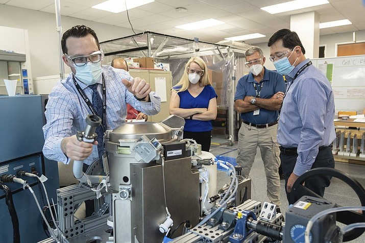 In this file photo provided by NASA, astronaut Kate Rubins, center, and support personnel review the Universal Waste Management System, a low-gravity space toilet, in Houston. The new device is scheduled to be delivered to the International Space Station on Oct. 1, 2020. (Norah Moran/NASA via AP)