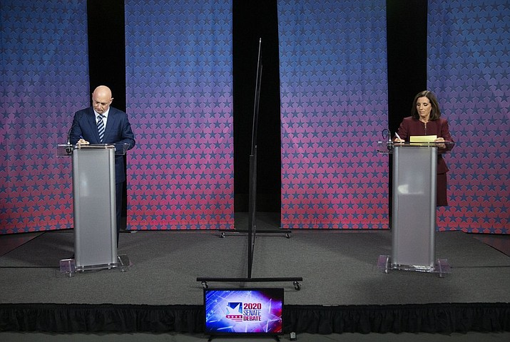 Democratic challenger Mark Kelly, left, and Republican U.S. Sen. Martha McSally prepare for their Senate debate, Tuesday, Oct. 6, 2020, at the Walter Cronkite School of Journalism at Arizona State University, in Phoenix. (Rob Schumacher/The Arizona Republic via AP, Pool)