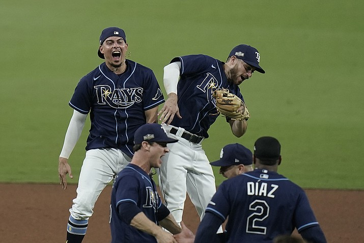 Tampa Bay Rays' Willy Adames, back left, and Brandon Lowe celebrate after the Rays defeated the New York Yankees 2-1 in Game 5 of a baseball AL Division Series, Friday, Oct. 9, 2020, in San Diego. (Jae C. Hong/AP)