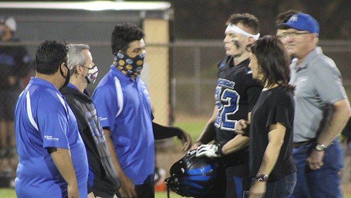 Kingman Academy High School senior quarterback Charlie Anderson is congratulated by coaches and accompanied by his parents during Senior Night festivities at Southside Park on Friday, Oct. 9. (Photo by Casey Jones/Kingman Miner)