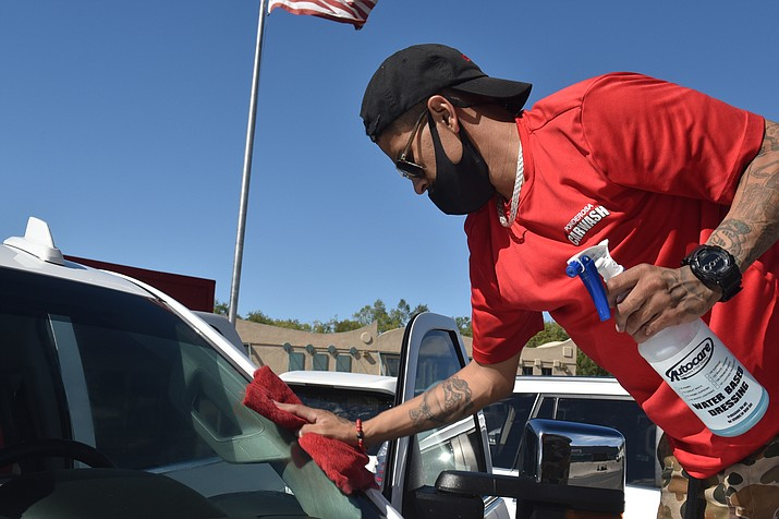 Matt Solis, 28, a finisher at Ponderosa Hand Car Wash, stands on a vehicle's tire to clean the windshield, on Friday, Oct. 20, 2020. (Jesse Bertel/Courier)