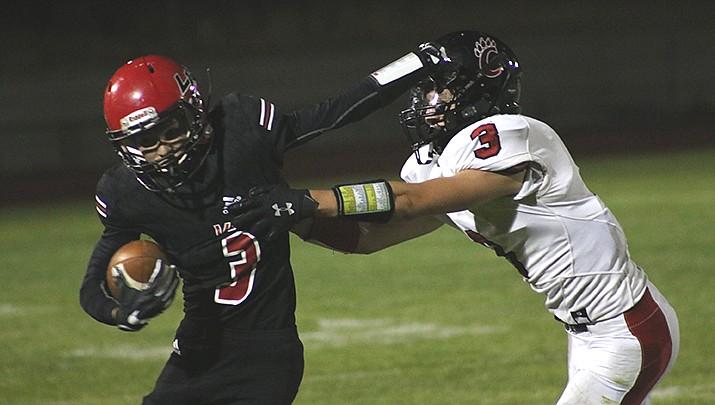 Senior wide receiver Rye Samson of Lee Williams High School stiff arms a Coconino defender on Friday, Oct. 9. (Photo by Travis Rains/Kingman Miner)