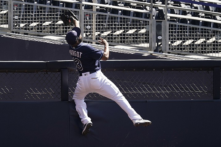Tampa Bay Rays right fielder Manuel Margot reaches over a right field wall after catching a foul ball by Houston Astros center fielder George Springer during the second inning in Game 2 of a baseball American League Championship Series, Monday, Oct. 12, 2020, in San Diego. (Jae C. Hong/AP)