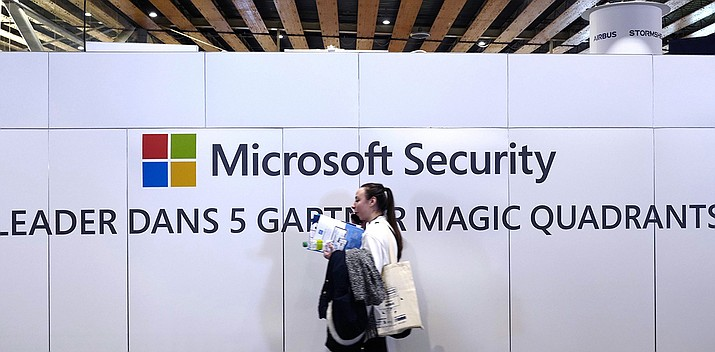 A woman walks in front of the Microsoft stand during the Cybersecurity Conference in Lille, northern France, Wednesday Jan. 29, 2020. Microsoft announced legal action Monday, Oct. 12, 2020 seeking to disrupt a major cybercrime digital network that uses more than 1 million zombie computers to loot bank accounts and spread ransomware, which experts consider a major threat to the U.S. presidential election. (Michel Spingler/AP)