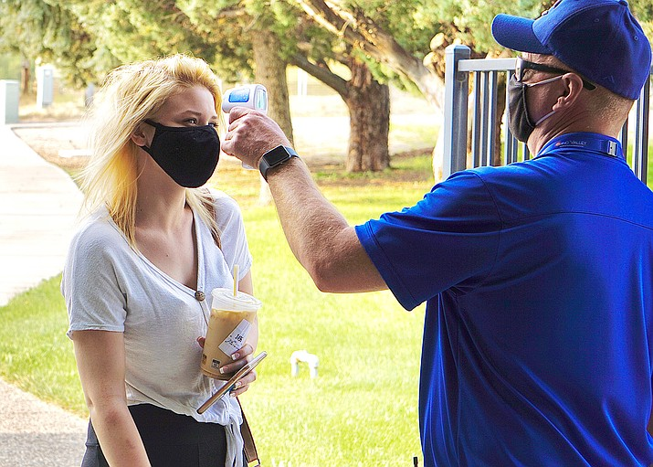 A Chino Valley High School staff member takes a student's temperature before she enters campus Sept. 8, 2020. (Aaron Valdez/Courier, file)