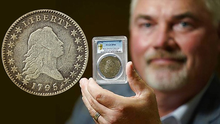 Bruce Morelan poses for a portrait holding a rare 1794 U.S. silver dollar, said to be among the first ever minted. Coin collecting experts had thought the Flowing Hair coin could sell for more than the $10 million Morelan spent to buy it in 2013. (John Locher/Associated Press)