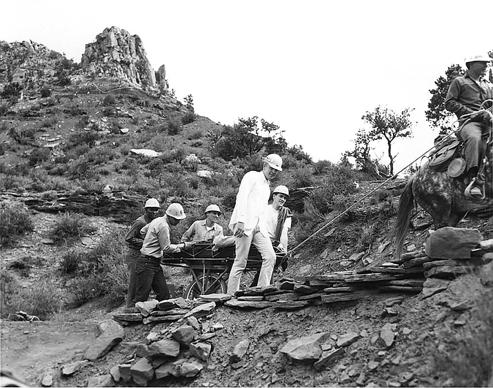 This historic image shows several men in hardhats carrying out another person on a litter—a basket with a single wheel in the middle. A man on a mule leads the way, with a rope tied to the litter. (Photo/NPS)