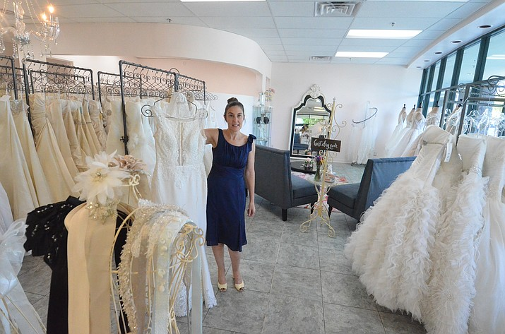 Michelle Furness shows one of her dresses at the new location of the Wedding Belle in Cottonwood on Friday. VVN/Vyto Starinskas