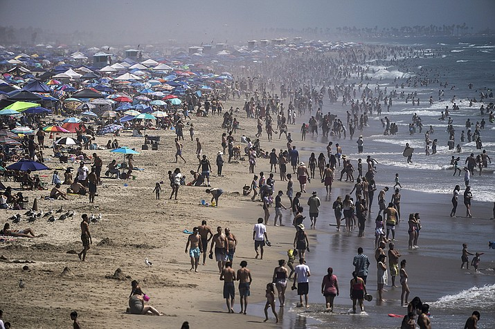 In this Saturday, Sept. 5, 2020 file photo, people crowd the beach in Huntington Beach, Calif., as the state swelters under a heat wave. On Wednesday, Oct. 14, 2020, the U.S. National Oceanic and Atmospheric Administration said the Earth reached a record hot September, saying that there's nearly a two-to-one chance that 2020 will end up as the globe's hottest year on record. (ae C. Hong/AP)