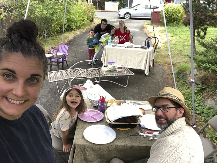 With COVID-19 making indoor dinners with friends a potential health risk, Jennifer Fliss, front left, held a socially-distanced Rosh Hashanah supper with neighbors in her Seattle driveway this year, as seen in this photo from Sept. 19, 2020. She'll likely do the same for Thanksgiving this year. (Jennifer Fliss via AP)