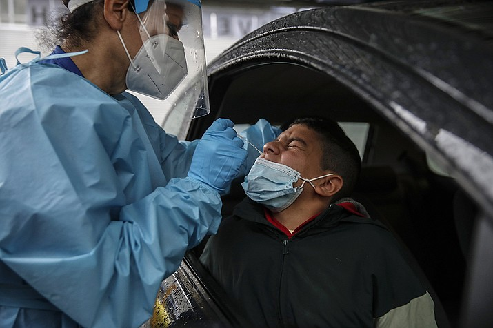 Medical staff takes a swabs as she tests a boy for COVID-19 at a drive-through at the San Paolo hospital, in Milan, Italy, Thursday, Oct. 15, 2020. Coronavirus infections are surging again in the region of northern Italy where the pandemic first took hold in Europe, renewing pressure on hospitals and health care workers. (Luca Bruno/AP)