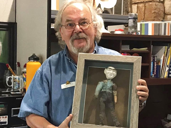 Jan Cassies, director of the Lake Havasu Visitor Center, poses with a doll on Wednesday, Oct. 7, 2020, that was buried for nearly 50 years inside the city's landmark London Bridge, in Lake Havasu City, Ariz. Tourism officials are still unsure what to do with the doll, which was found in 2018. (Brandon Messick/Today's News-Herald)