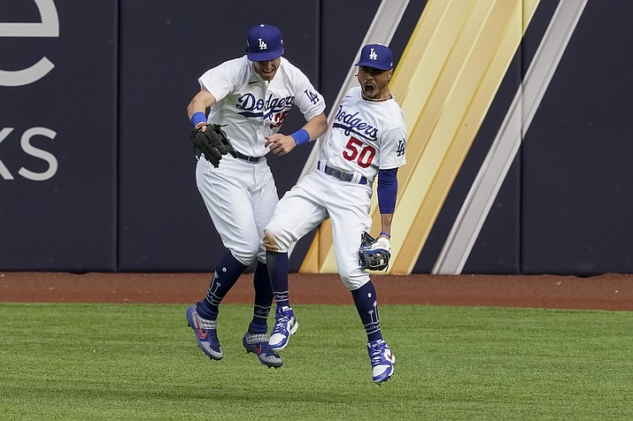 Los Angeles Dodgers right fielder Mookie Betts celebrates with center fielder Cody Bellinger after robbing Atlanta Braves' Marcell Ozuna of a home during the fifth inning in Game 6 of a baseball National League Championship Series Saturday, Oct. 17, 2020, in Arlington, Texas. (Tony Gutierrez/AP)