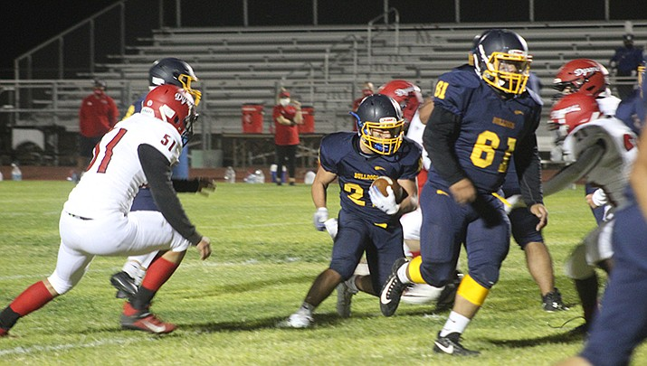 Nick Williams-Garcia (21) runs the ball for Kingman while Joey Benson (61) blocks. (Photo by Casey Jones/Kingman Miner)