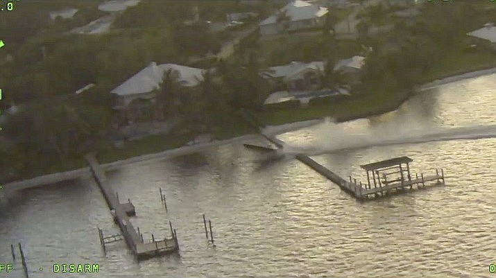 This Saturday, Oct. 10, 2020, photo provided by the Martin County Sheriff's Office shows an unmanned boat going over a dock on the St. Lucie River in Florida. Three people conducting a photo shoot on the boat somehow fell overboard, leaving the 24-foot vessel unmanned and out of control. (Martin County Sheriff's Office via AP)