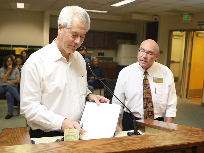 """Author Dan Jackson signs two copies of his newest novel """"Rainbow Bridge,"""" during his presentation at a Chino Valley Town Council meeting on Tuesday, Oct. 13, 2020, in Chino Valley. Jackson donated two copies of his book to the Chino Valley Public Library. (Town of Chino Valley, Facebook/Courtesy)"""