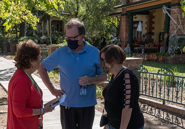 """Yavapai College President Lisa Rhine, right, and James Rhine, center, receive information from Amer-ican Association of University Women (AAUW) member Lynn Murphy along Mount Vernon Ave. on Oct. 17, 2020, during AAUW's scholarship fundraiser, """"A Stroll Through Victorian Prescott."""" The event, which in conjunction with the Yavapai College Foundation, is aimed at benefiting the Yavapai College AAUW Centennial Scholarship, a fund that supports female students taking STEM (Science, Technology, Engineering or Math) programs. It continues from 2 to 4 p.m. Saturday, Oct. 24. For more information, visit aauwprescott.net. (Deb Dillion/Courtesy)"""