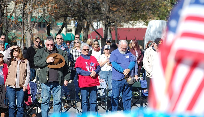 Parade-goers bow their heads as the U.S. Flag is displayed during the opening ceremony of the 2018 Prescott Veterans Day Parade. The 2020 parade will be held on Wednesday, Nov. 11. (Tim Wiederaenders/Courier, file)