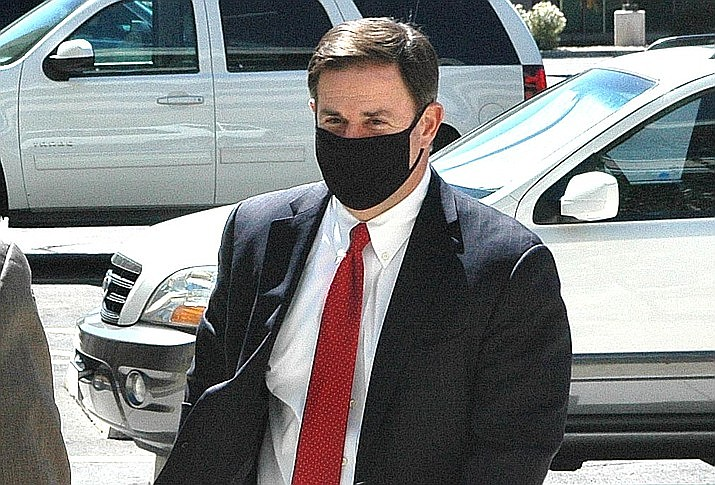 Arizona Gov. Doug Ducey wears a masks at a June news conference. Democrat presidential hopeful Joe Biden called out the Republican governor on Friday over his failure to implement a statewide mask mandate. Capitol Media Services / Howard Fischer file photo