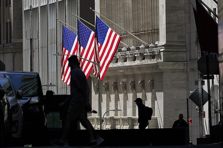 n this Oct. 14, 2020 file photo, pedestrians pass the New York Stock Exchange.  Stocks are mixed on Wall Street, following gains in European markets, as more U.S. companies report encouraging results for the summer earnings period. (Frank Franklin II/AP)