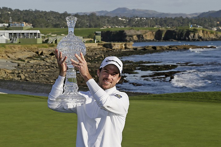 In this Feb. 9, 2020, file photo, Nick Taylor, of Canada, holds up his trophy on the 18th green of the Pebble Beach Golf Links after winning the AT&T Pebble Beach National Pro-Am golf tournament in Pebble Beach, Calif. The win got him into his first Masters, but Taylor will miss out on the roars without spectators. (Eric Risberg, AP File)