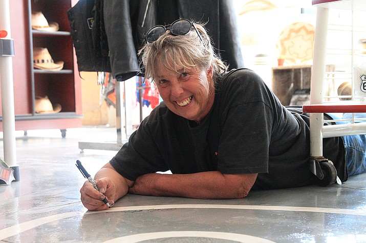 Donna Hovet signs a Route 66 mural she completed in 2016 on the floor of Zettlers Market. Hovet is now working on a 30 foot Route 66 mural on the roof of Zettlers. (Loretta McKenney/WGCN)